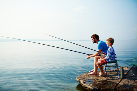 Young man and little boy fishing together