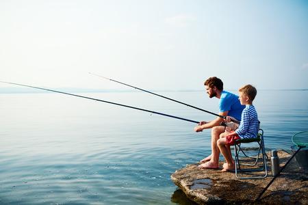 Jonge man en kleine jongen die samen vissen