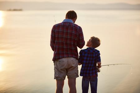 pesca: Niño pequeño y su padre de pesca al atardecer