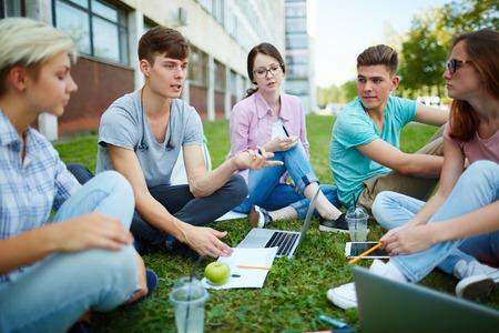 revising: Teenage groupmates revising home task outdoors