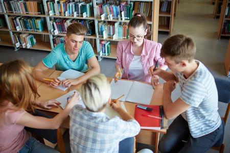 schoolwork: Group of teenage groupmates doing schoolwork together Stock Photo