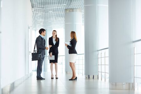 Elegant managers talking in corridor of business center Stock Photo