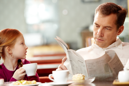 absorbed: Little girl talking to her father absorbed in newspaper Stock Photo