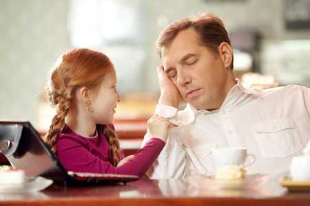 nagging: Little daughter bothering her father falling asleep in cafe Stock Photo