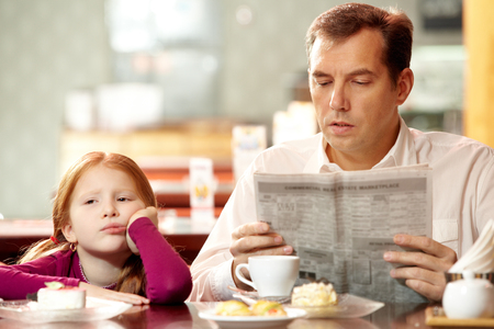dad and daughter: Bored girl sitting in cafe with her father who is reading paper Stock Photo