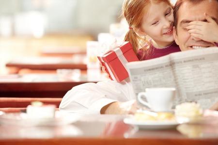 Niña que cubre sus ojos padres con una mano y con caja de regalo en la otra