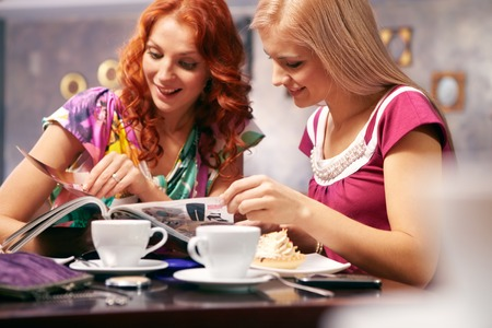fashion magazine: Two young girls turning over pages of fashion magazine in cafe Stock Photo