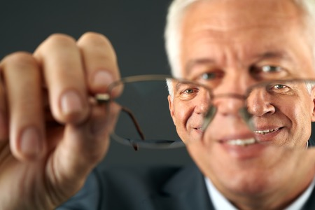 Close-up of eyeglasses and man looking through them