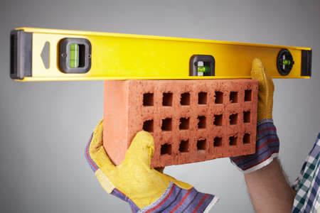 manual measuring instrument: Close-up of brick being measured with a level