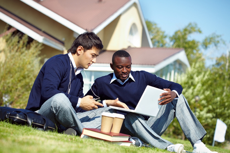 private schools: Two students having break in campus and using laptop Stock Photo