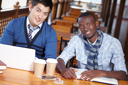 Portrait of two student guys sitting at table, looking at camera and smiling Stock Photo