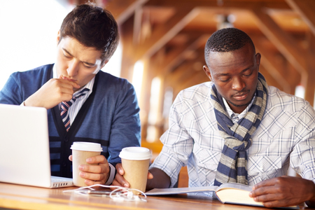 assignments: Two young students sitting in cafe absorbed in their assignments