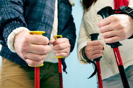 elderly adults: Close-up of ski poles holding by people