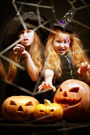 Portrait of little aggressive Halloween girls with pumpkins Imagens