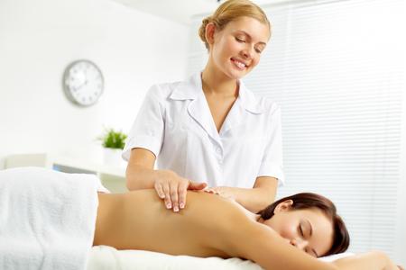 Young masseur massaging a woman