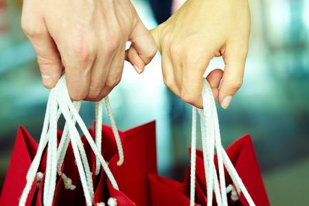 dedo meÑique: Dos manos unidas con bolsas de la compra