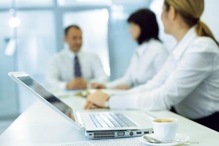 gente comunicandose: Ordenador portátil y una taza de café sobre la mesa con la gente de negocios que comunica en el fondo Foto de archivo