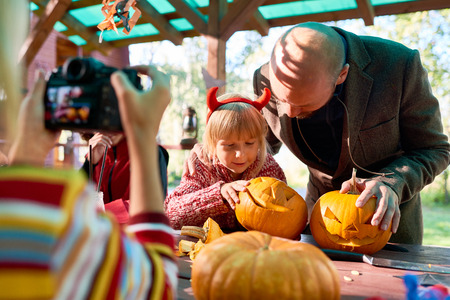 Father and daughter looking at Halloween pumpkins