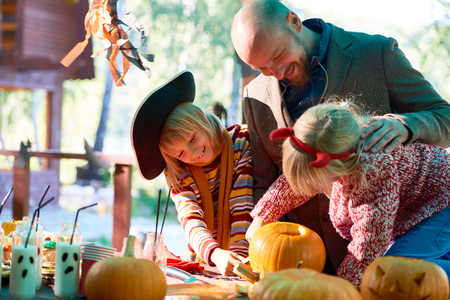 holiday tradition: Happy man and his daughters looking at Halloween symbols