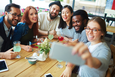 ecstatic: Ecstatic friends making selfie by table in cafe