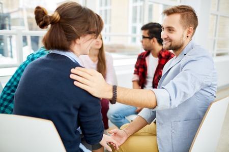 reassuring: Smiling guy reassuring girl during psychological course Stock Photo