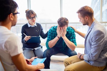 Groupmates geruststellend één van de vrienden bij psychologische cursus