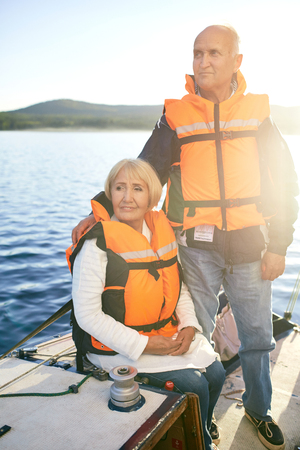 lifevest: Retired couple in life-vests yachting at leisure