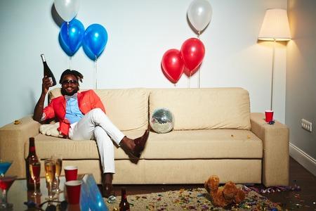 African Mann mit der Flasche Champgne auf dem Sofa zu sitzen Partei