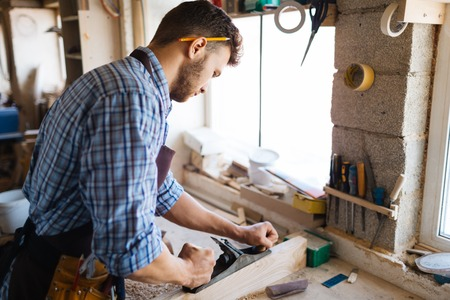 planing: Young carpenter planing wooden plank