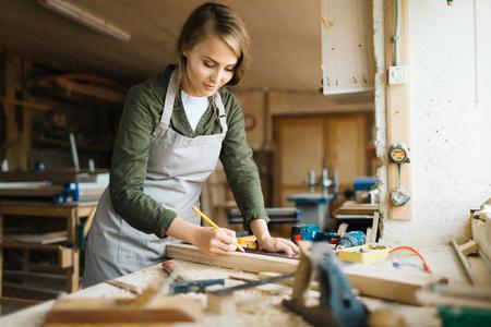 若い女性のワーク ショップで木の板を測定