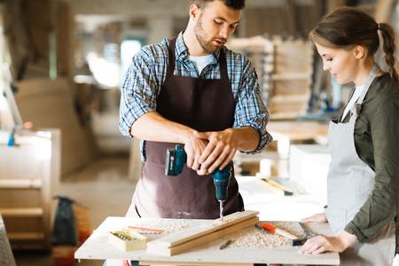 taladro: Joven carpintero mostrando a su asistente cómo utilizar el taladro