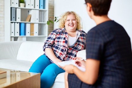 Happy patient with overweight talking to her psychologist