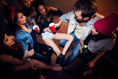 Small company of stylish young people talking to each other and drinking beer in quiet room at big house party, high angle shot