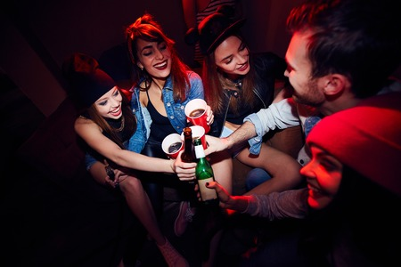 cool guy: High angle of several young people, girls and one man, getting drunk at club party, sitting close together in dark red lit room and cheering to their meeting Stock Photo
