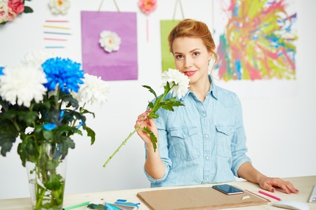 smelling: Young woman designer smelling a flower in her office