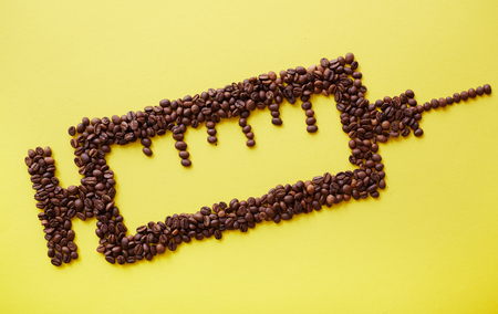 ailing: Coffee beans in shape of syringe on yellow background