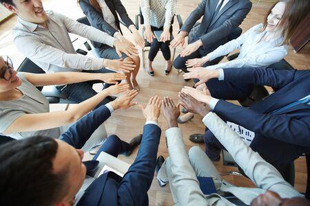 huddling: Business colleagues huddling hands at training