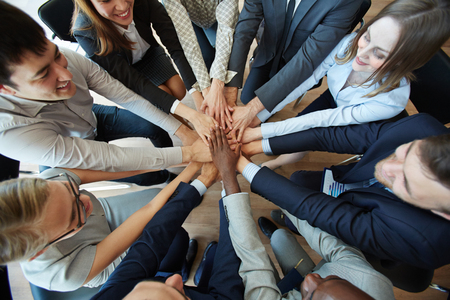 Business people heaping hands in circle to show their loyalty