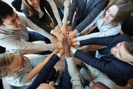 Mensen uit het bedrijfsleven stapelen handen in een cirkel om hun loyaliteit te tonen