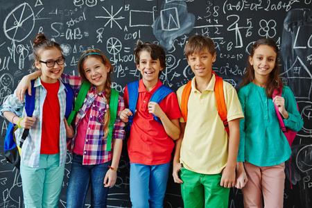 黒板に立って幸せな小学生がノートと笑顔で覆われて