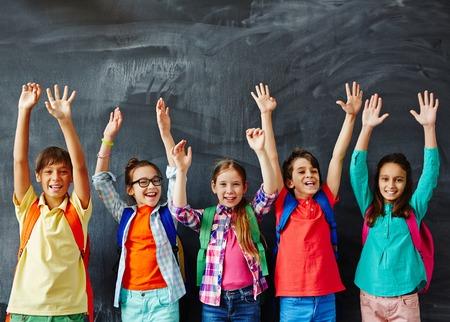 raising: Schoolkids raising hands at chalkboard