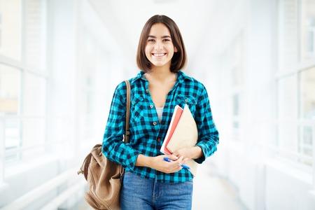 캐주얼웨어 미소를 카메라에 긍정적 인 여자 학생 스톡 콘텐츠