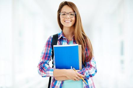 Portret van een tiener student in glazen glimlachen op camera