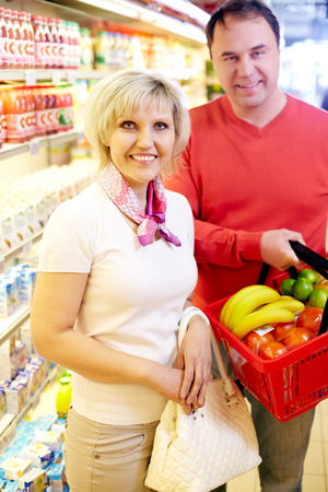 Portrait of mature couple in grocery with shopping basket full of food 版權商用圖片