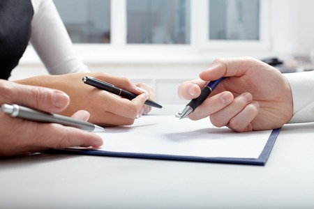 three hands: Three hands with pens over document Stock Photo