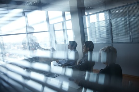 blackout: Business meeting of four people in black-out office room Stock Photo