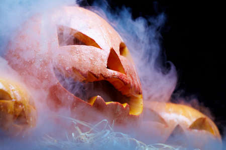 Close up of Jack O Lantern smoking among two other pumpkins against black background Stock Photo