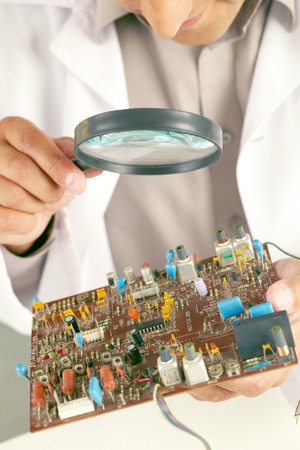 Man examining transistor with the help of magnifying glass