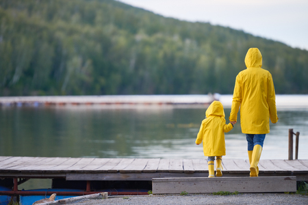 Rear view of woman and child in yellow raincoats and rubberboots walking towards river