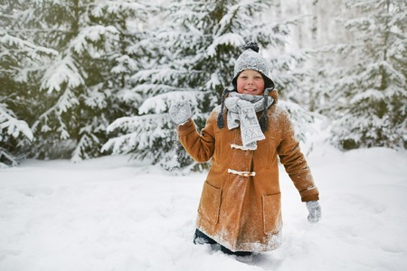 Happy boy in winterwear playing snowballs in park Stock Photo